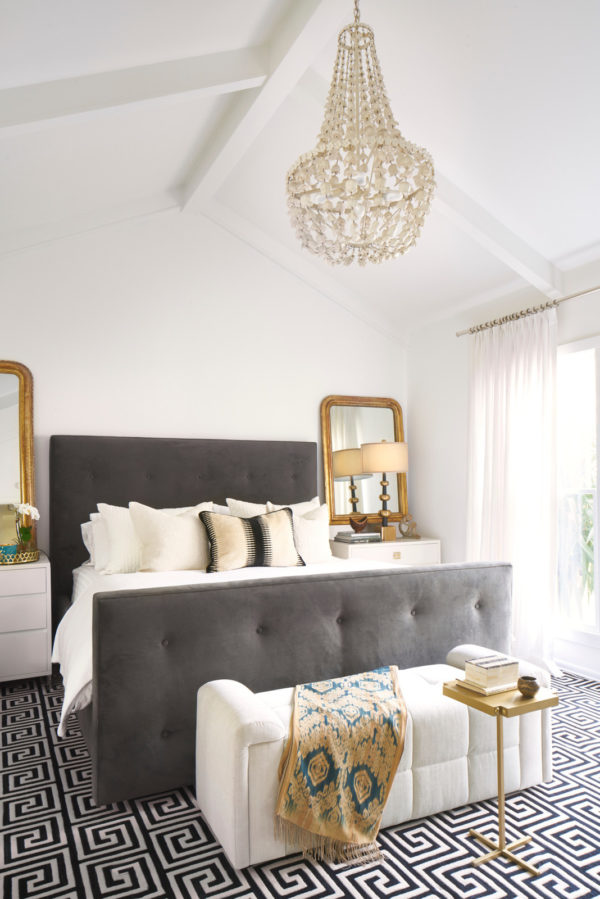 an eclectic sanctuary of white bedroom highlighted by gold throw, lamps, and mirrors