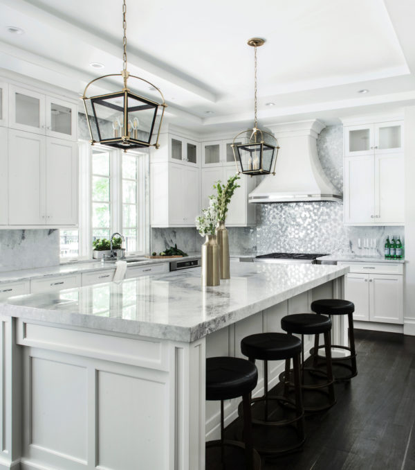 sophisticated white kitchen bursting with grand marble surfaces and stainless appliances