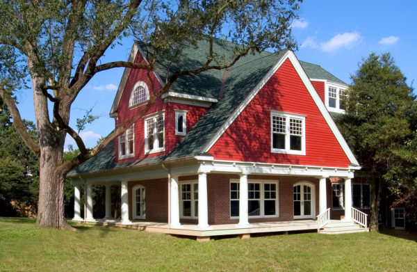 a funky red brick house looks stunning with red siding and green gable roof color