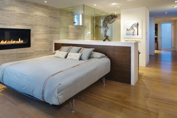 elegant headboard half wall with storage for open concept bedroom and shower area