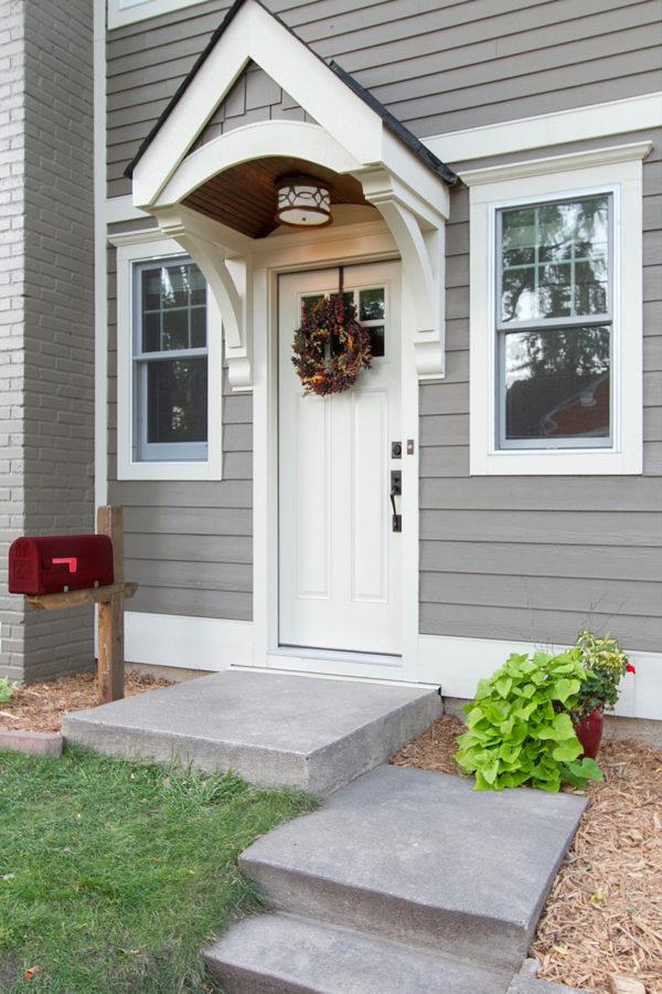 raw concrete front steps to match a grey farmhouse design exterior