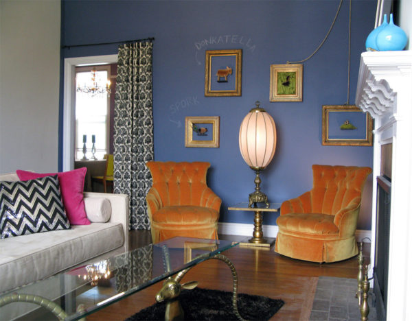 a personalized blue living room with chalk embellishments, gold side chairs, and antique lamps