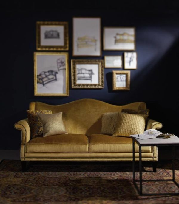 create a stunning formal living room featuring navy blue walls, gold frames, and gold couch