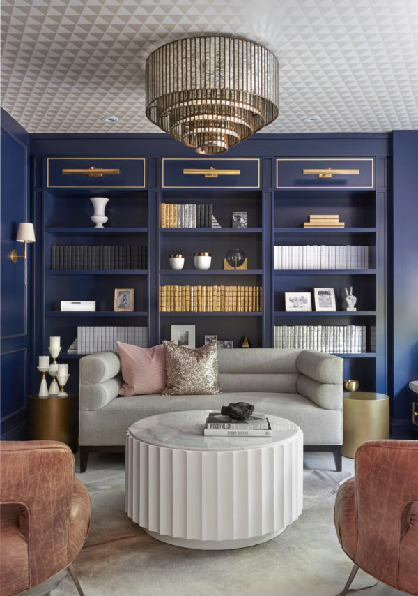 high-class living room with royal blue built-in bookcase and gold accents
