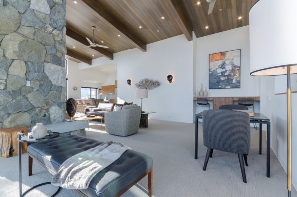 a formal white and gray living room mixes stone wall and wood ceilings for a minimalist yet natural vibe