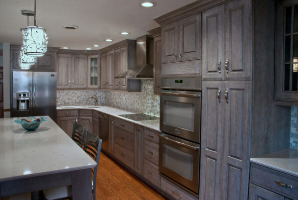 a gorgeous all-grey kitchen with grey cabinets, mosaic backsplash, and medium toned wood floor