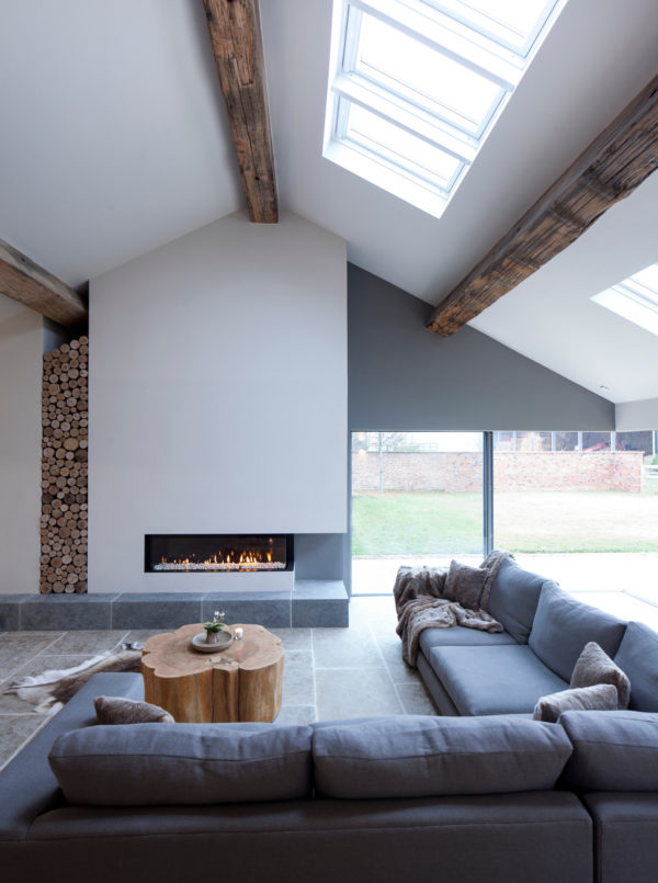 barn lounge combines white walls and natural wood beams with comfy l-shaped gray couch
