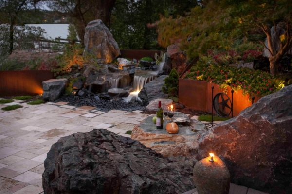 combine corten steel retaining wall and stone sculptures with warm lighting for a dark yet sophisticated landscape