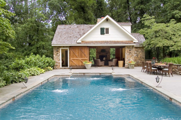 country pool house and bathroom with classic barn doors to complete an oversized swimming pool