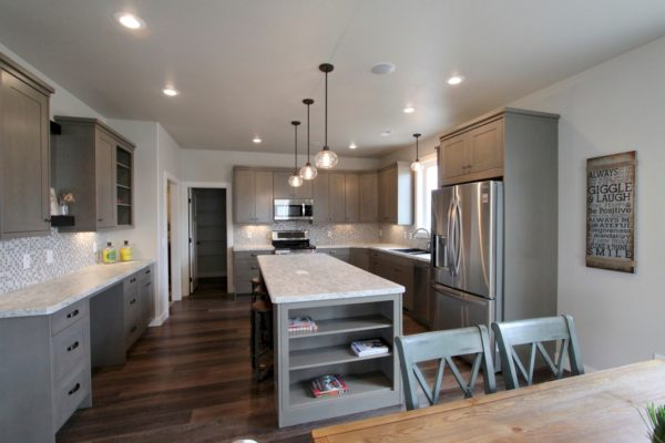 create a cozy eat-in kitchen featuring modern grey-stained cabinets and a modest island with built-in shelves
