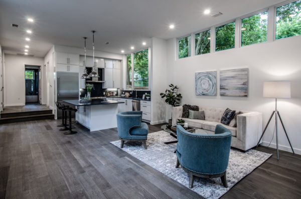 embrace farmhouse style with an open kitchen and living room featuring gray wood flooring and white walls