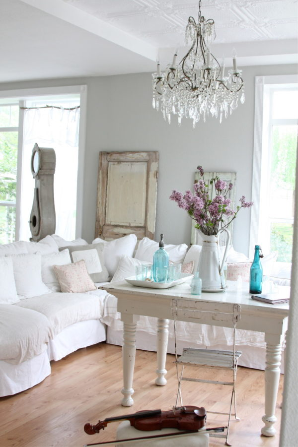 hang a crystal chandelier for some sophistication in this modern living room with gray walls and white fabric couch