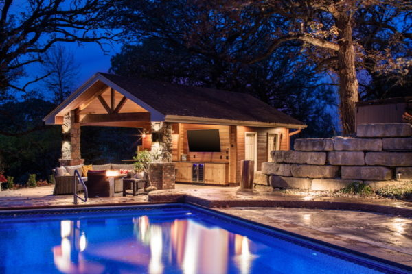 large craftsman pool house with a cozy bathroom to complete this charming stone backyard