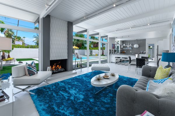 open concept living space with white floors and ceilings, gray walls, and doors that open to the backyard