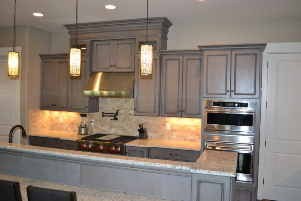 opt for a simple kitchen with grey-stained cabinets and warm pendant lights