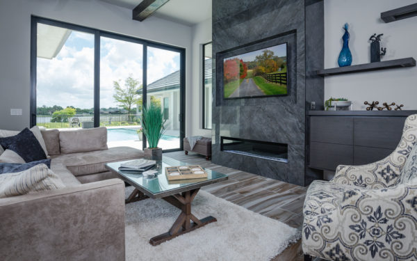 polished porcelain tile for linear fireplace and wall-mounted tv on gray walls make for a soothing living space