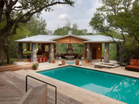 try a c-shaped pavilion around a fire pit for a cozy pool house with bathroom