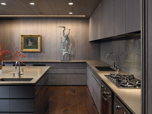 try a contemporary kitchen featuring grey-stained cabinets, grey wall panels, and lagos blue countertops