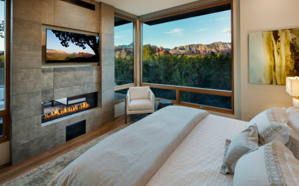 try a two-sided linear fireplace and mounted tv on stone accent wall for a small yet cozy contemporary master bedroom