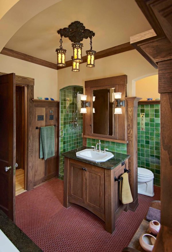 a craftsman inspired master bathroom with green mosaic walls and antique brown cabinets