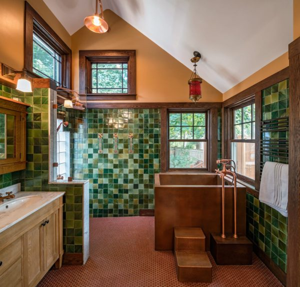 a dark and cozy craftsman bathroom pairs brown walls with multi-shaded green mosaic tiles