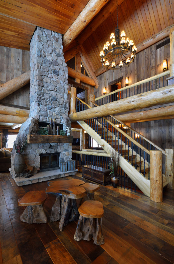 beautiful living room in a log cabin featuring dramatic stone fireplace and wood furniture