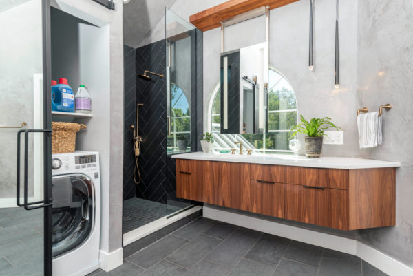 black tiled shower and hidden washing machine for an exquisite bathroom and laundry room combo