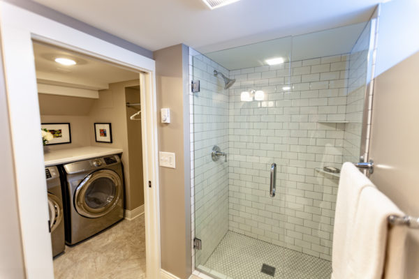 build a mini laundry room connected to the bathroom with beige walls and tiled shower