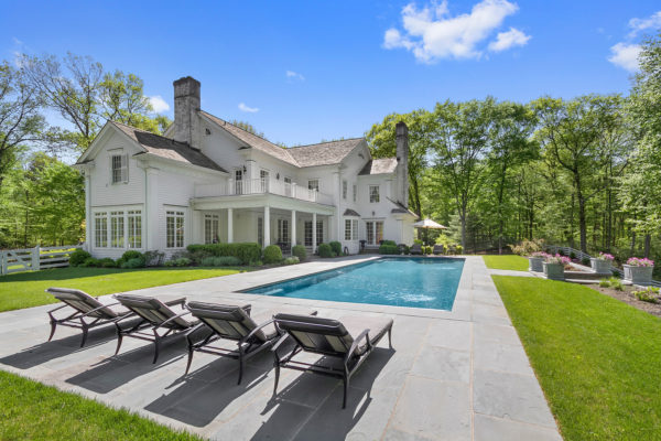 can't go wrong with a simple rectangular pool and stamped concrete deck to complement a colonial home exterior