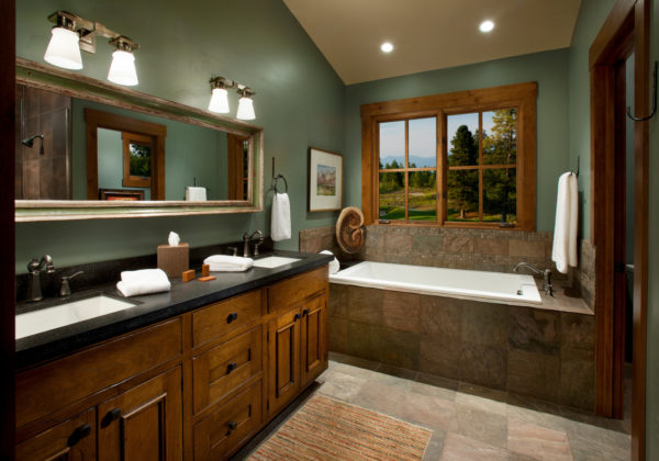 evoke rustic vibes in this mountain style bathroom featuring green walls and brown furniture