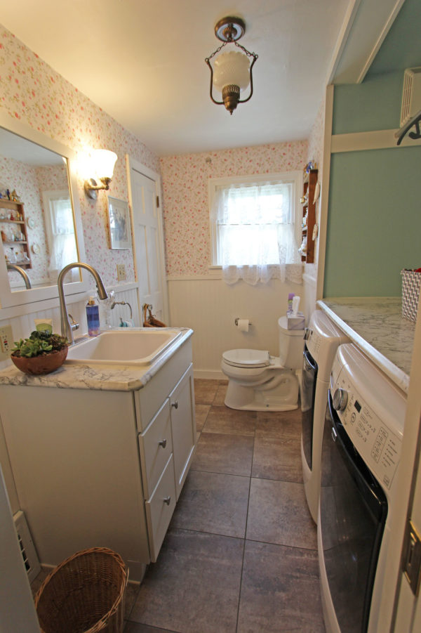 farmhouse bathroom and laundry combo has built-in countertop and floral wallpaper