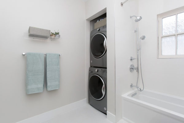 furnish bathroom laundry room combo with stainless-steel accents and clear glass shelf