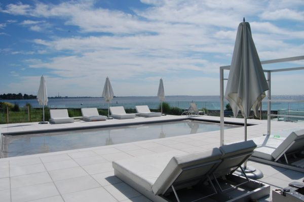 furnish stamped concrete tiles for a picturesque pool deck with multiple sun loungers for a resort-like vibe