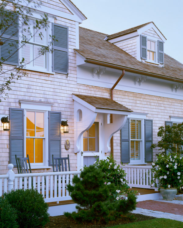 go for a charming exterior featuring a roof over door entry, gray clapboards, and white fence