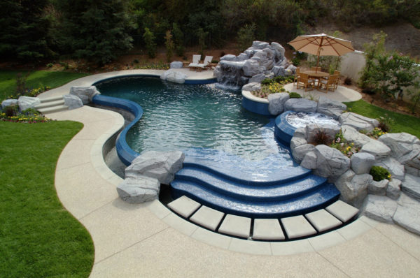 go for a custom-shaped pool in a classic backyard design with stamped concrete deck and stunning water features