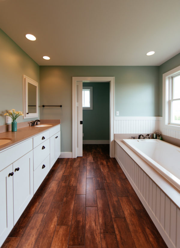 go for a spacious contemporary bathroom with brown wood flooring and pastel green paint