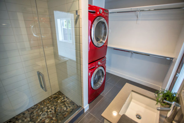 metallic red washer and dryer in this modern bathroom and laundry combo with clothes hangers