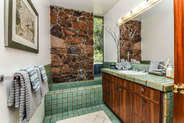 mid-century bathroom that feels natural features green floor alcove tub and brown stone tiles