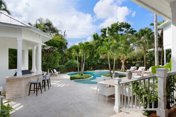 pair stamped concrete pool deck with palm trees and outdoor bar for a beachside resort style backyard
