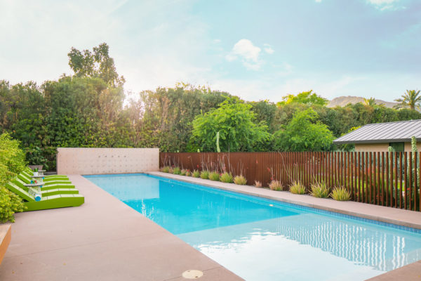 round off your stamped concrete pool deck with horizontal wood fencing and green sunbeds