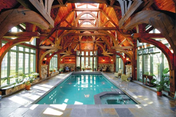 rustic indoor pool featuring stamped concrete deck and opulent vaulted ceilings