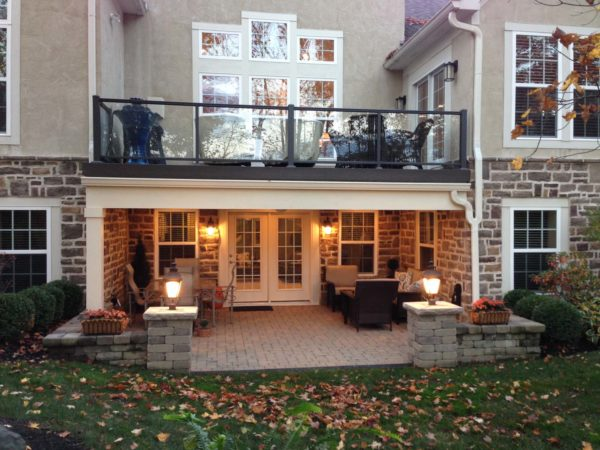 set up a comfy second-story deck over warm patio complete with glass railings