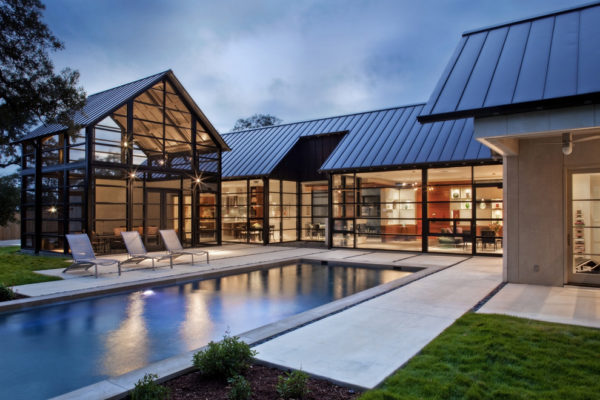 stamped concrete pool deck can look trendy in front of an all-glass house exterior