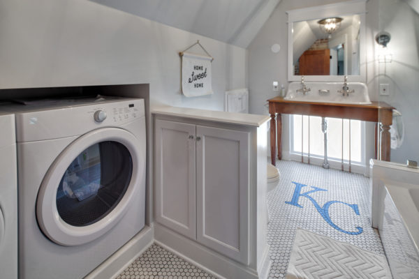 this bathroom laundry combo with cottage charm features custom ceramic tile flooring