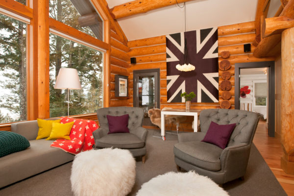 trendy log cabin living room features contemporary wall art and champagne armchairs