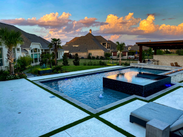 try a modern pool deck using stamped concrete, tropical plantings, and a contemporary cabana