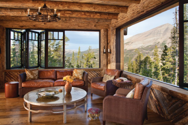 use bifold windows to blend log cabin living room with the stunning landscape outside