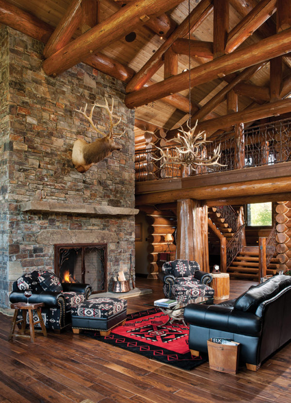 use floor-to-ceiling moss rock fireplaces in a rustic handcrafted log cabin living room
