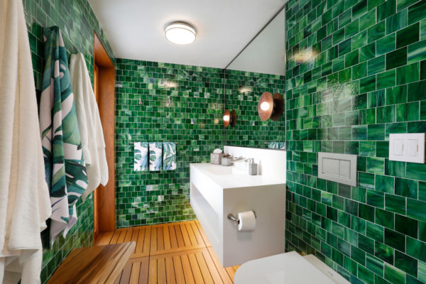 use mosaic tiles for fun green walls that complement the simple brown flooring