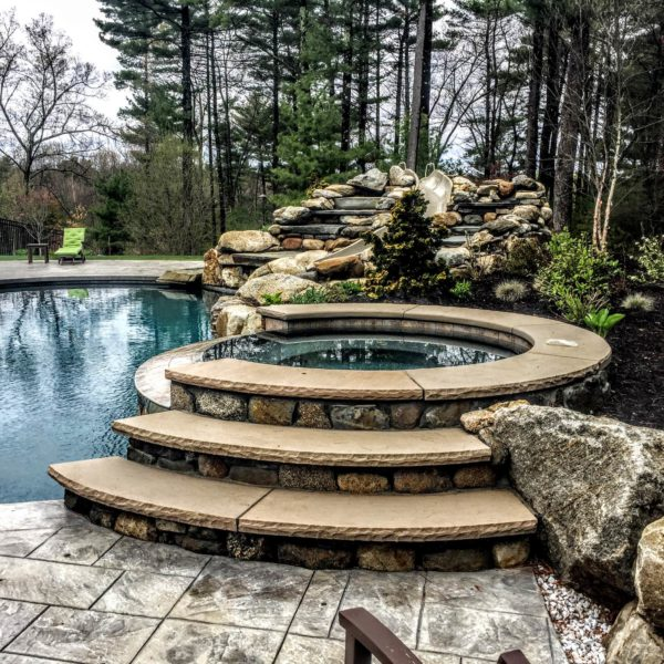 use stamped concrete for the pool deck in a timeless backyard surrounded by lush forests